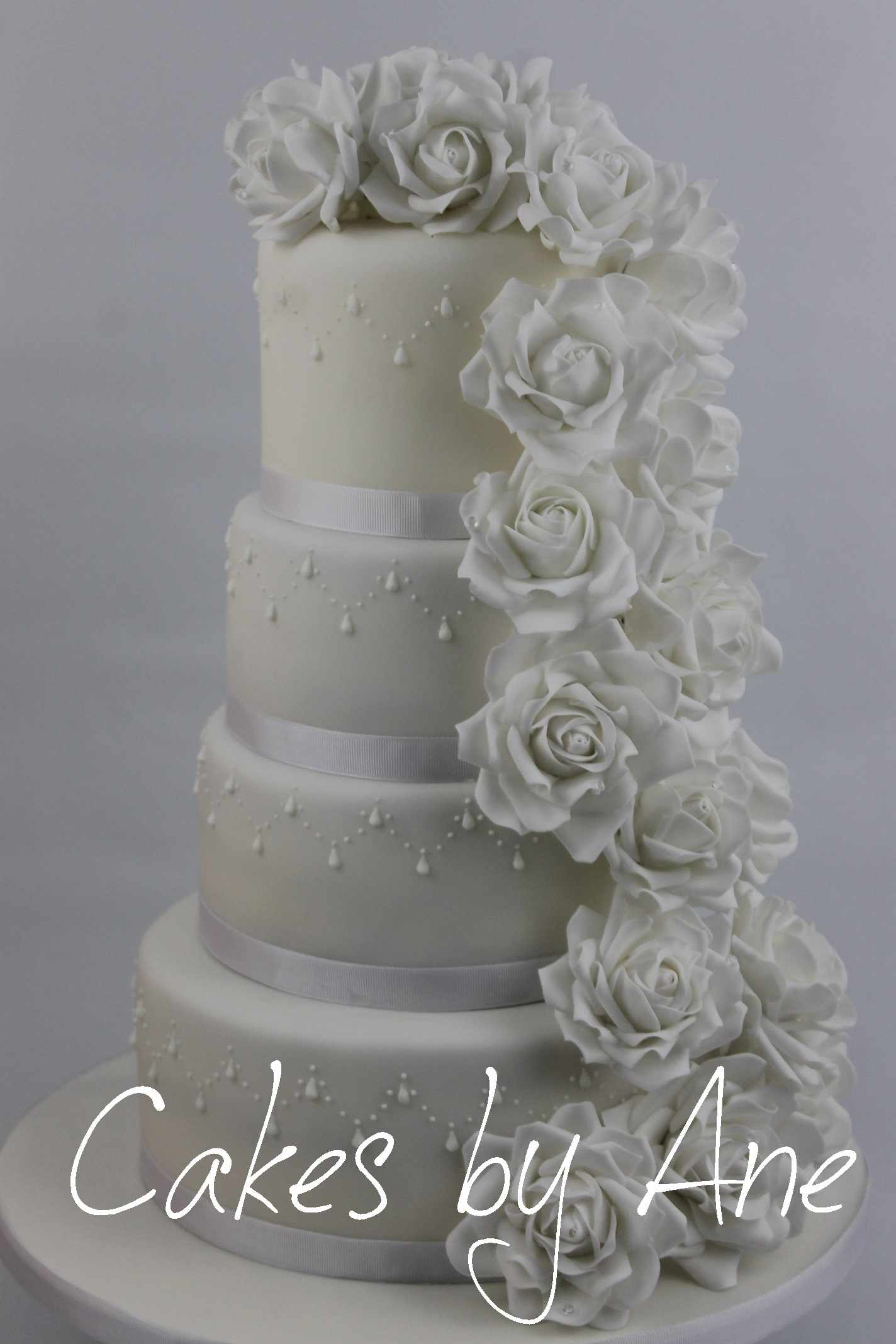 An Elegant Wedding Cake With A Flowing Arrangement Of White Roses